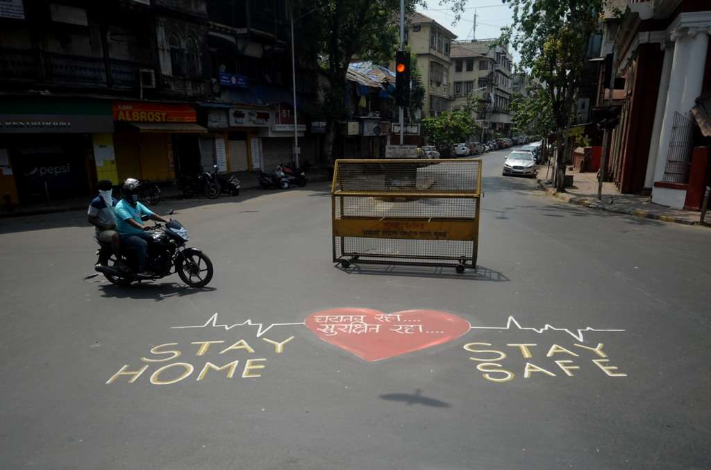 Biker rides his bike near a painting apealing people to stay at home in Mumbai